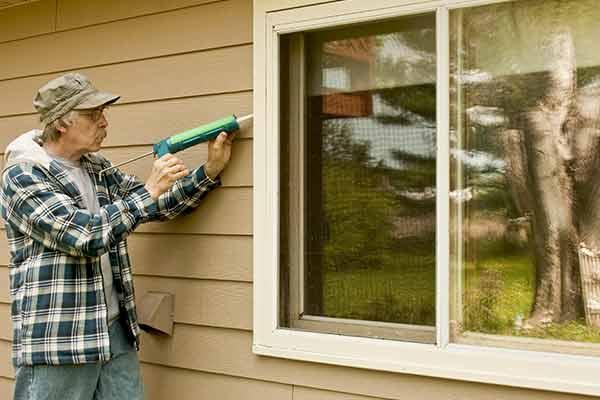 man caulking between window and siding