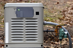 Gray home backup generator sitting outdoors