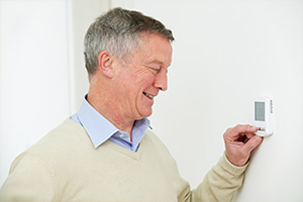 Older man contentedly changing temperature on wall mounted thermostat