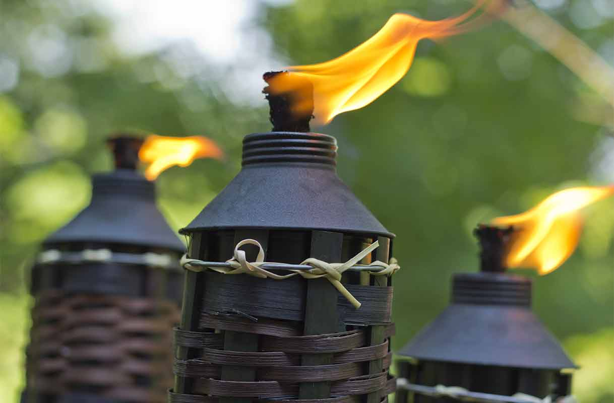 close-up of lit citronella tiki torch