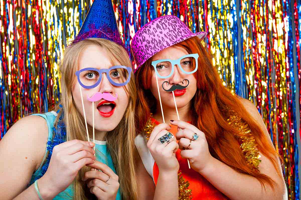 girls pose with props in a dance party photo booth