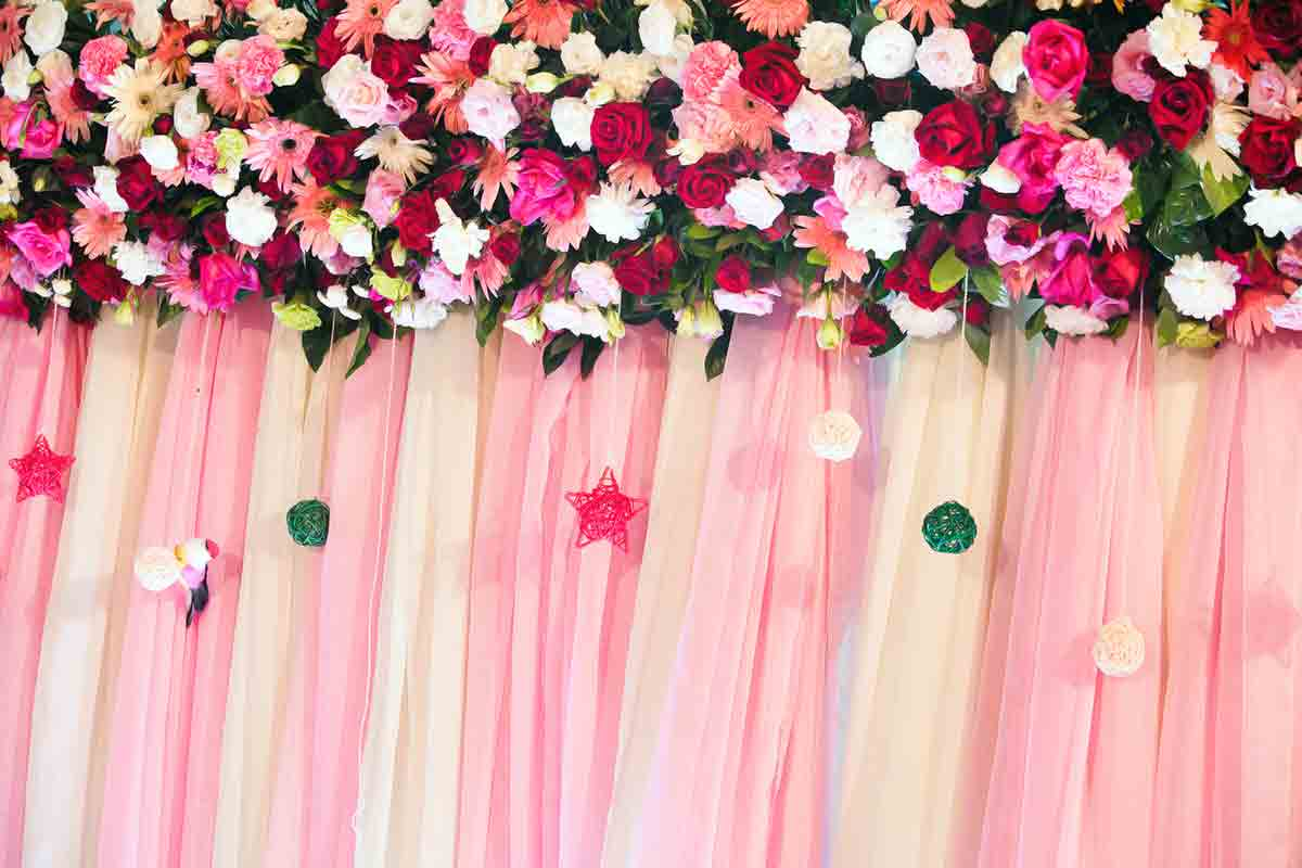 wedding photo booth backdrop with flowers along the top