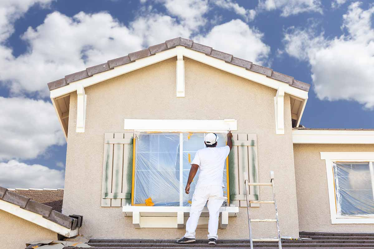 man painting exterior of house - Exterior Coatings For Houses