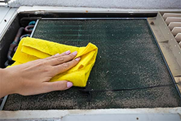 hand cleaning dirty air filter with yellow rag