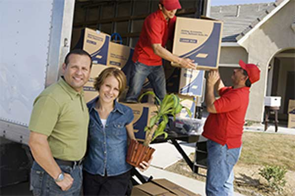 couple loading moving truck with boxes and plant