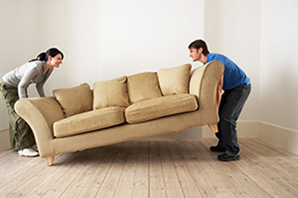 couple moving couch into new home
