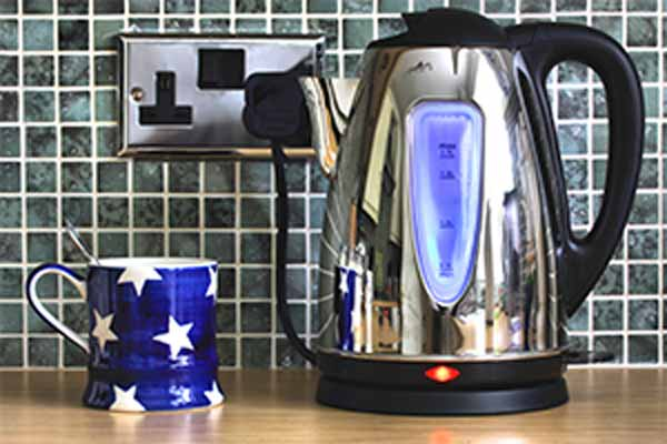 electric kettle plugged into outlet next to coffee mug