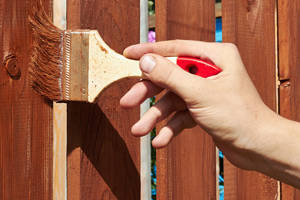 hand painting a wood fence brown