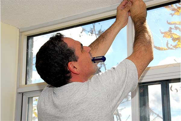 man working on window in home