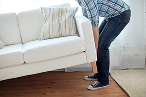 Person lifting one end of white couch off wooden floor