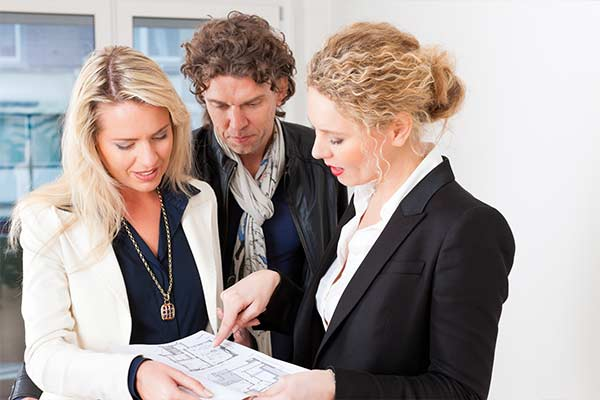 realtor discusses paperwork with two renters