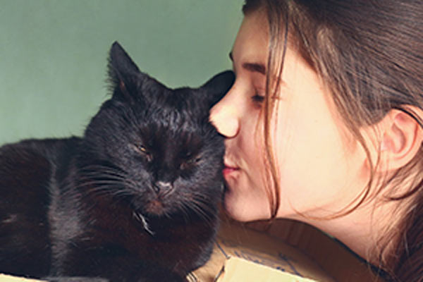 teenage girl kisses black cat