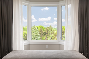 view of blue sky and trees through bay window with curtains