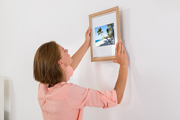 woman removing picture frame from wall