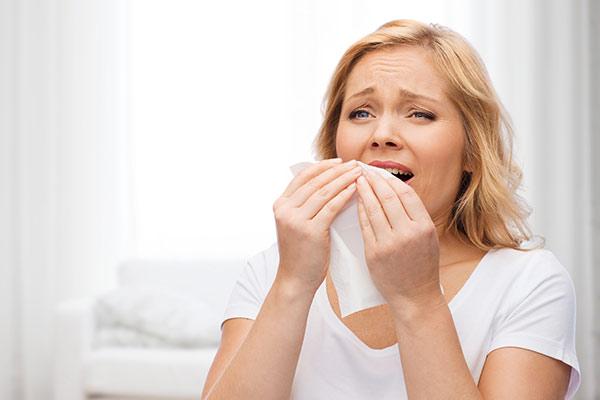 woman sneezing into napkin