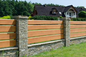 wood fence with stone posts in front of house